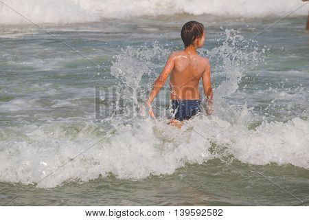 Boy Frolics In The Sea With Splashes And Waves