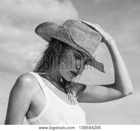 Portrait of beautiful young woman with straw hat on a sunny day  over sky and trees landscape. Black and white photo - face closeup of pretty girl with straw hat pattern shadow on her face