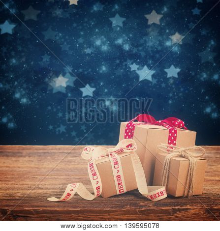 Pile of Handmade gift boxes on wooden table, stary night at background, retro toned