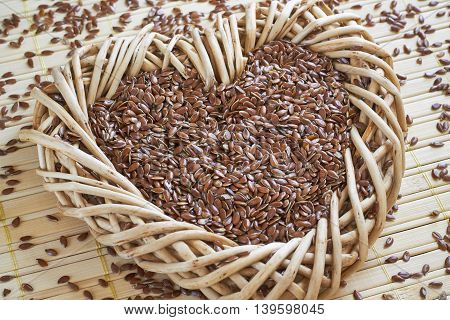 Flax seed in woven heart-shaped basket with flaxseed scattered around on bright wooden background.