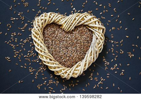 Flax seed in woven heart-shaped basket with flaxseed scattered around on dark background