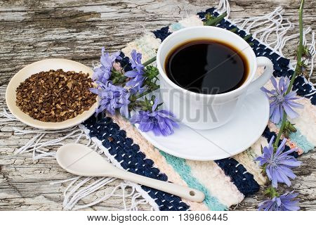 Medicinal plant chicory: flowers and ground roots. The roots of the plants are used as a substitute for coffee. Drink from chicory in a cup on the old wooden background. Rustic style selective focus