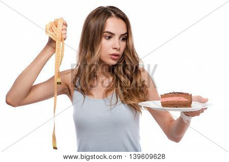 Real dilemma. Pleasant baffled woman holding plate with cake and measure tape and choosing between them while standing isolated on white background