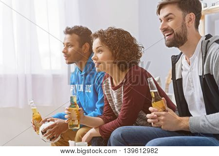 Drinks and sports with friends. Cropped photo of football fans cheering on sofa with beers on sofa, sitting in row