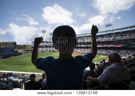 Child standing and cheering at a baseball game. Silhouette view from behind poster