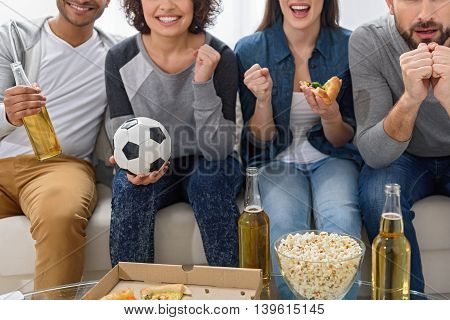The coolest football fans. Close up of sports fans at home watching game on tv and cheering for their team goal