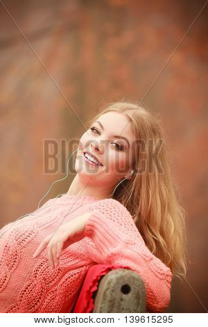 Autumn concept people outside spare time. Attractive woman sitting on the bench. Girl is relaxing in the park in autumnal weather.