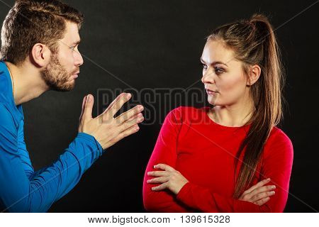 Husband apologizing upset angry wife. Man asking woman for forgivness. Boyfriend trying to convince girlfriend. Conflicted couple in studio on black. Relationship problem.