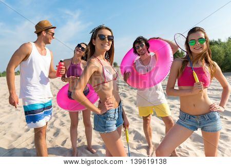 Young and reckless. Cheerful smiling happy friends resting on the beach together while expressing joy
