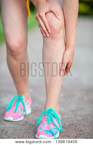 Female athlete suffering from pain in leg while exercising