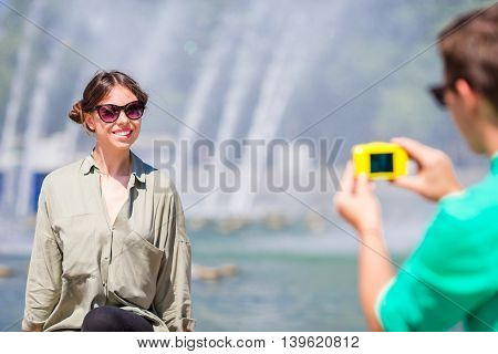 Man taking a picture of his friend while sitting next to a fountain