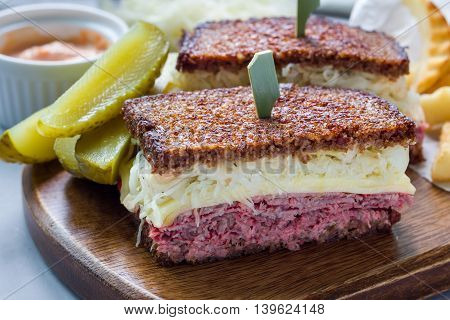 Classic reuben sandwich with corned beef swiss cheese sauerkraut and thousand island dressing on pumpernickel bread served with dill pickle spear and potato chips horizontal