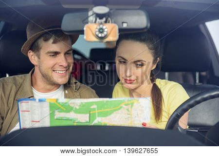 Cheerful tourists making romantic trip. They are sitting in car and reading map. Man and woman are smiling