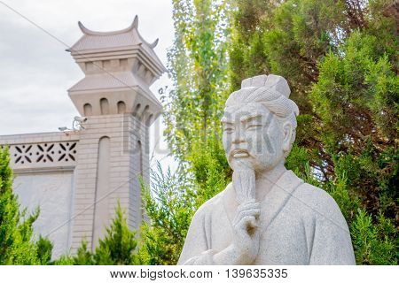 Xinjiang China 09/06/2015 Stone statue of Confucius in front of trees and a Chinese tower is touching his beard with a thinking expression