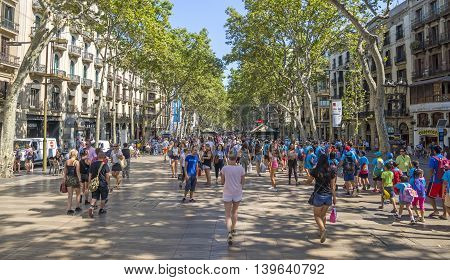 BARCELONA SPAIN - JULY 5 2016: Hundreds of people promenading in the busiest street of Barcelona the Ramblas. The street extends 1.2 kilometers connects the Placa de Catalunya in the centre with the Christopher Columbus Monument at Port Vell.
