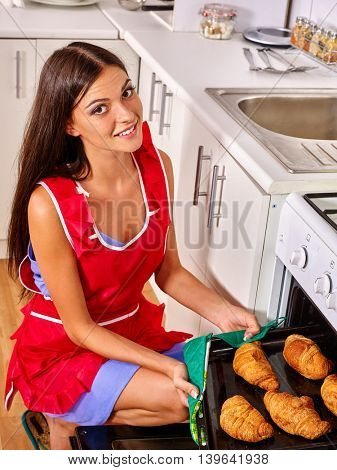 Young woman bake croissants at home kitchen. Woman oven croissants at kitchen.