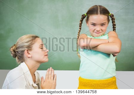 Female teacher apologizing girl in the classroom at school