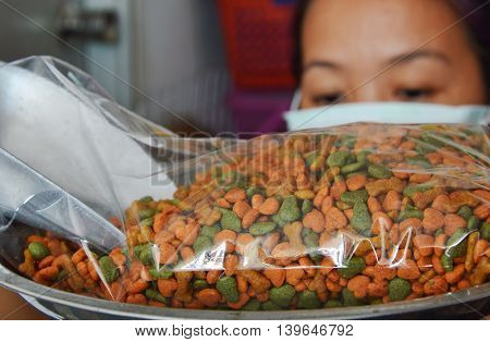 woman weight dog food in plastic bag for packing
