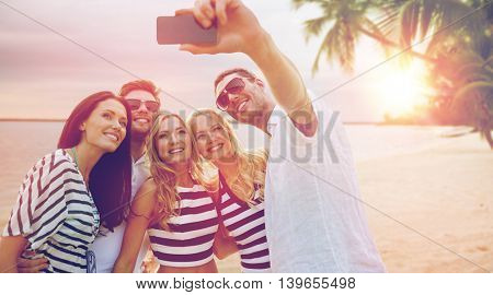 summer holidays, travel, tourism, technology and people concept - group of smiling friends with smartphone photographing and taking selfie over exotic tropical beach background