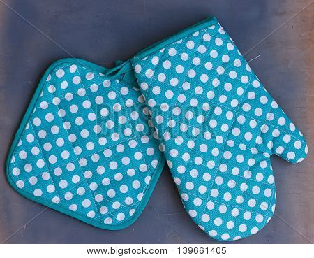 Oven mitt or potholder on the wooden background.