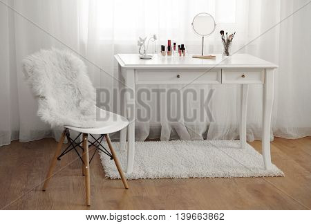 Dressing table with cosmetics in room