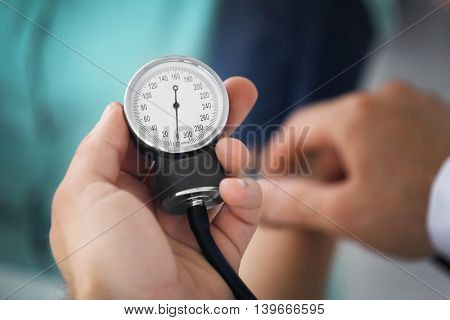 Male hand holding medical manometer and measuring blood pressure