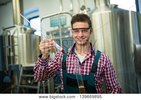 Portrait of brewer testing beer at brewery factory