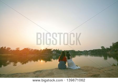Two beautiful woman sit on the waterside in Khao Yai,  thailand