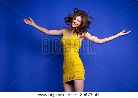 Portrait of beautiful smiling model with flying hair jumping with arms widened on blue background.Isolate