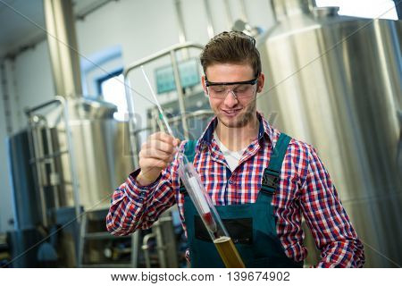 Brewer testing beer at brewery factory