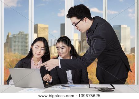 Image of middle eastern businessman talking with two multi ethnic businesswomen in the office