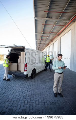 View of manager is using a tablet in front of workers are loading a truck in front of a warehouse