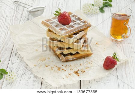 Homemade baking. Viennese waffles with powdered sugar and strawberry on wrapping paper.