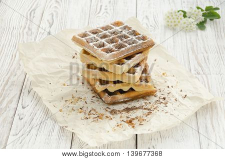 Homemade baking. Viennese waffles with powdered sugar and chocolate on wrapping paper.