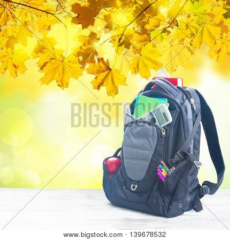 School backpack with supplies on white desktop, fall tree leaves in background