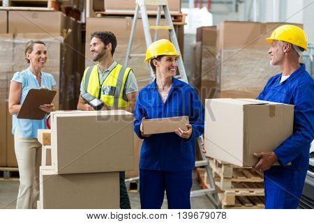 Workers carrying boxes in warehouse