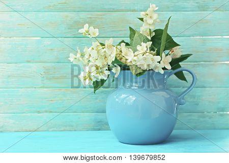 Fresh jasmine flowers in a vase on wooden background