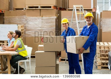 Smiling workers looking at camera in warehouse