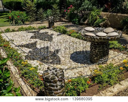 SEA OF GALILEE, ISRAEL - OCTOBER 20: Stone mosaic composition - two fish and five loaves of bread in landscape park, Church of Mount of Beatitudes at the Sea of Galilee, Israel on October 20, 2015
