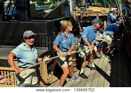 Mystic Connecticut- July 11 2015: Crew members on deck pulling heavy rope aboard the 1841 Charles W. Morgan whaling ship at Mystic Seaport