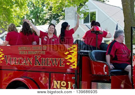 WEST ST. PAUL, MINNESOTA - MAY 21, 2016: Lady Ferty and Vulcan Krewe of Saint Paul Winter Carnival lore in red fire truck wave to crowd during annual West St. Paul Days Grande Parade in West St. Paul on May 21.