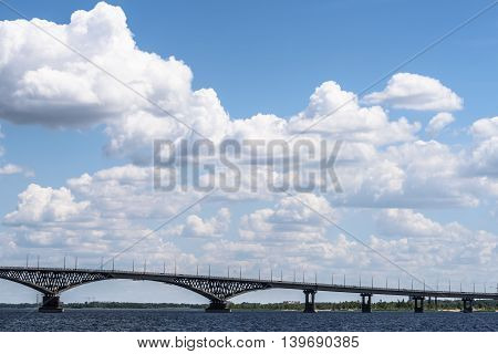 Impressive landscape of the beautiful white clouds in the blue sky above the bridge between the cities of Saratov and Engels through the river Volga
