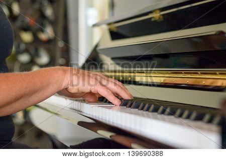 Hand of a woman playing the piano indoors at home in a close up view conceptual of a musical hobby entertainment or classical recital