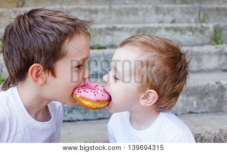 two kids bite off a donut and having fun. two boys together bite from the donut. children enjoy a donut with strawberry frosting. divide the a donut in half. feeding game for party