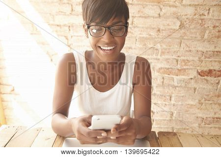 Quick Message To Friend. Attractive Young African Woman Holding Smart Phone, Using Photo Editing App