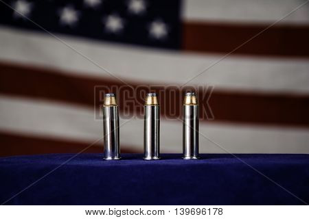 three 357 magnum bullets on blue in front of american flag