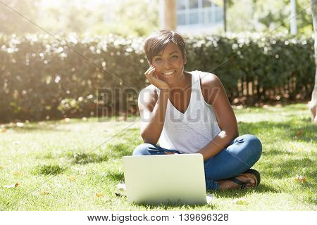 Young Successful African American Woman Blogger Sitting In The Park On The Grass, Writing A New Post