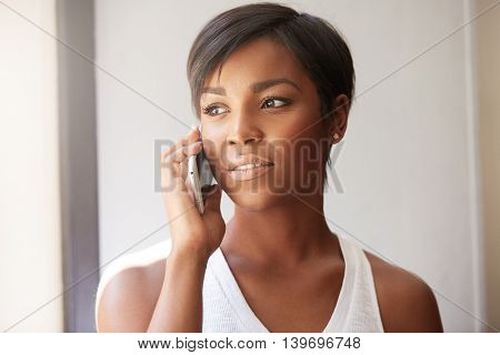 Indoor Portrait Of Attractive Young Dark Skinned African Woman, Using Cell Phone For Ordering Pizza