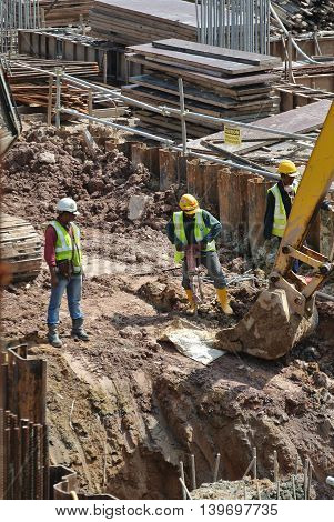 MALACCA, MALAYSIA -MAY 13, 2016: Construction workers working at the construction site at Malacca, Malaysia during daytime. They are wearing proper safety gear so ensure they are safe working.
