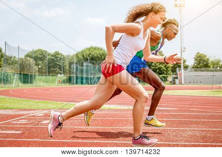 atheletes running at the stadium on runners track